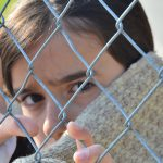 Photo of a child behind a fence