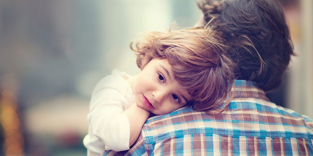 A young girl resting her head on her father's shoulder.