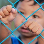 Child behind fence